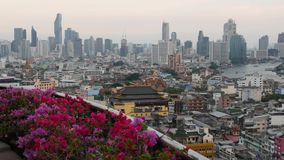 Vista de constru??es tradicionais e modernas da cidade oriental Canteiro de flores bonito contra a arquitetura da cidade de casas vídeos de arquivo