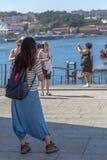 Vista de docas de Ribeira na baixa de Porto, com a menina do turista que toma imagens com telefone, turistas e rio de Douro no fu fotos de stock royalty free