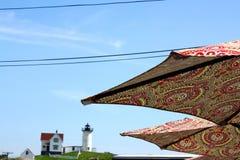 Vista de dois guarda-chuvas da cópia de paisley com o farol do Nubble no fundo fotos de stock