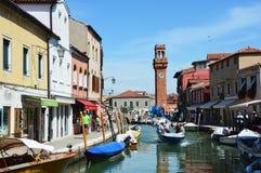 Vista de edificios y del canal con los turistas y los barcos en Murano, una pequeña ciudad agradable encima de la isla Fotos de archivo