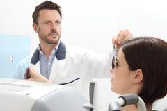 Vista de examen del optometrista, paciente de la mujer que señala en ho foto de archivo libre de regalías