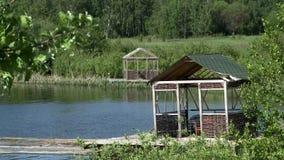 Vista de gazebos de mimbre en el lago almacen de metraje de vídeo