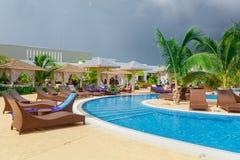 Vista de invitación de una piscina cómoda abierta de par en par curvada con la gente que relaja y que disfruta de su tiempo Fotografía de archivo libre de regalías