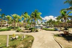 vista de invitación de los argumentos del hotel, del jardín tropical y de la piscina con la gente que camina, relajándose y nadan Foto de archivo libre de regalías