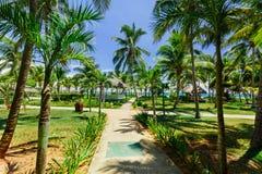 Vista de invitación natural de los argumentos del hotel con el jardín tropical en día agradable soleado Foto de archivo