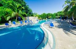 Vista de invitación que sorprende de una piscina en jardín tropical con la gente que se relaja en fondo Foto de archivo