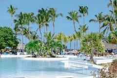 Vista de invitación de la piscina tropical del jardín en día hermoso soleado Foto de archivo libre de regalías