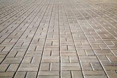 Vista de la acera, alineada con las tejas cuadradas de la calle, con perspectiva fotos de archivo