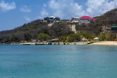 Vista de la bahía, de la playa y del embarcadero del silbido de la sal con los barcos y las palmeras, Mayreau, el Caribe del este Foto de archivo libre de regalías