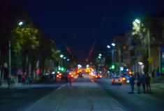 Vista de la calle en la ciudad en la noche borrosa, donde montando los coches, las luces del resplandor de las tranvías y las lin Imágenes de archivo libres de regalías