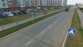 Vista de la calle rusa típica en verano con los nuevos edificios, el camino, los coches, los senderos y la gente que camina escen almacen de video