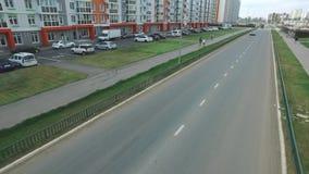 Vista de la calle rusa típica en verano con los nuevos edificios, el camino, los coches, los senderos y la gente que camina escen almacen de metraje de vídeo