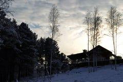 Vista de la casa en una colina entre el bosque nevoso en los rayos del sol poniente en invierno fotos de archivo