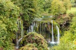 Vista de la cascada pedregosa y del pequeño río Foto de archivo