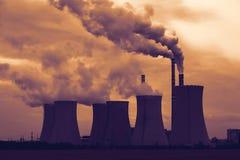 Vista de la central eléctrica de energía del carbón que fuma en la puesta del sol Fotografía de archivo
