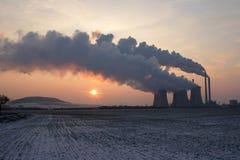 Vista de la central eléctrica del carbón contra el sol y humos enormes Fotos de archivo libres de regalías