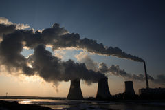 Vista de la central eléctrica del carbón contra el sol y humos enormes Foto de archivo libre de regalías