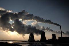 Vista de la central eléctrica del carbón contra el sol y humos enormes imágenes de archivo libres de regalías