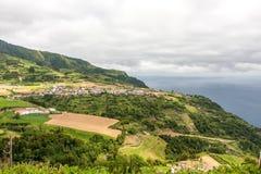 Vista de la ciudad con las granjas en las montañas cerca del mar imágenes de archivo libres de regalías
