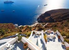 Vista de la ciudad de Fira - isla de Santorini, Creta, Grecia Balcones concretos blancos del hotel que lleva abajo a la bahía her Foto de archivo libre de regalías