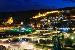 Vista de la ciudad de Rike Park Old, del puente de Metekhi y de la iglesia y de la fortaleza de Narikala en la noche Tbilisi, Geo Foto de archivo libre de regalías