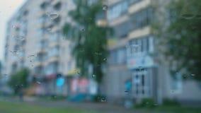 Vista de la ciudad de la ventanilla del coche a través de la lluvia blur almacen de video