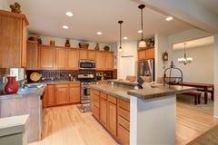 Vista de la cocina con la combinación del almacenamiento de la madera dura, la barra y las luces del colgante fotos de archivo libres de regalías
