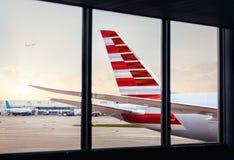 Vista de la cola del fuselaje del aeroplano a través de la ventana en el aeropuerto imagenes de archivo