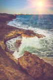 Vista de la costa rocosa, de las ondas que hacen espuma del mar y de la ciudad en la distancia en la puesta del sol Foto de archivo