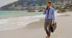 vista de la vista delantera del hombre de negocios caucásico que camina con la cartera en la playa 4k metrajes