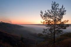 Vista de la distancia nebulosa con las colinas y la salida del sol Imagen de archivo libre de regalías