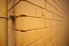 Vista de la esquina de una pared de ladrillo anaranjada del modelo del color imagen de archivo