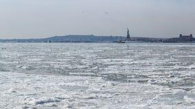 Vista de la estatua de la libertad y de Jersey City a través de Hudson River congelado Imágenes de archivo libres de regalías