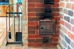 Vista de la estufa y del primer de los accesorios en un país de madera h Fotos de archivo libres de regalías