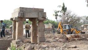 Vista de la gente, del cavador y del camión en las ruinas en uno de los templos en Hampi almacen de video