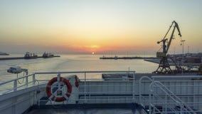 Vista de la grúa del puerto y la salida del sol de la cubierta de la nave foto de archivo libre de regalías