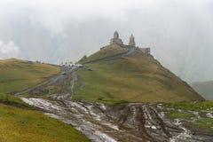 Vista de la iglesia de la trinidad de Gergeti a través del camino borroso por la lluvia Stepantsminda, Georgia Imágenes de archivo libres de regalías