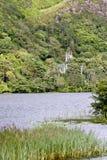 Vista de la iglesia neogótica en el estado de Kylemore, a través del lago, al oeste de Irlanda Foto de archivo