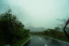 Vista de la manera de camino y del Mountain View borrosos con la gota de agua en el coche Fotografía de archivo