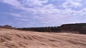 Vista de la mina escena Emplazamiento de la obra del paisaje con la mina y arena en el fondo de pasar el tren de carga almacen de metraje de vídeo
