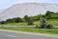 Vista de la mina de sal y de un montón artificial con la hierba verde en el primero plano foto de archivo