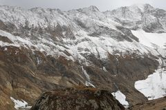 Vista de la montaña montañosa nevosa debajo de las nubes oscuras imagenes de archivo