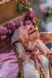 Vista de la muñeca del granjero, manipulada con la gente dentro, llevando la cesta tradicional grande, en el mercado medieval de  fotos de archivo