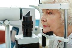 Vista de la mujer mayor que verifica por el aparato Fotos de archivo libres de regalías