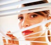 Vista de la mujer a través de la persiana Imágenes de archivo libres de regalías