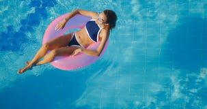 Vista de la natación morena joven de la mujer en el anillo rosado inflable imágenes de archivo libres de regalías