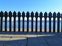 Vista de la orilla opuesta a través de la cerca imagen de archivo libre de regalías