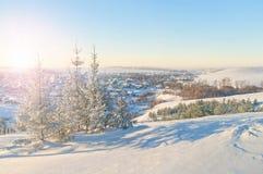 Vista de la pequeña ciudad del invierno en la puesta del sol de la cumbre Imagen de archivo libre de regalías