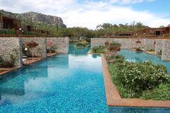 Vista de la piscina azul y de los chalets elegantes en el hotel de lujo Fotos de archivo libres de regalías