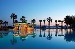Vista de la piscina, de la barra de la piscina y de las palmeras en la puesta del sol en h turco Fotografía de archivo libre de regalías